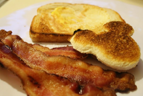 Mickey House Shaped Egg-in-a-Hole, Mickey Mouse Ear Toast, and Bacon on a white plate.