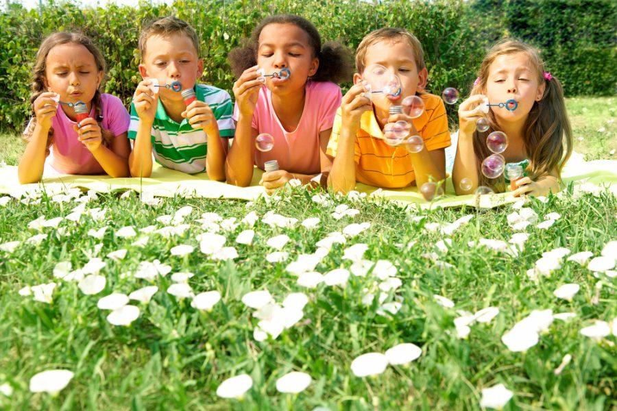 portrait of cute friends having bubble fun on green lawn in park