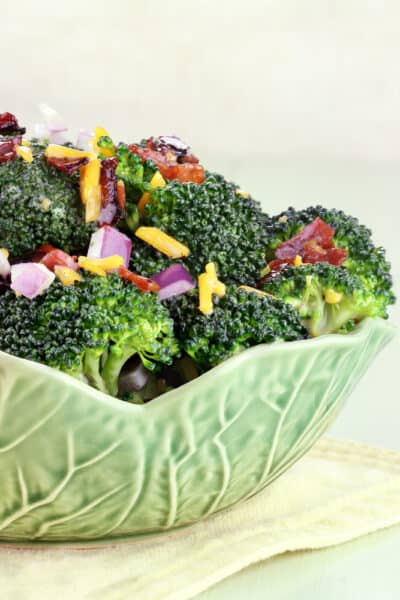 Green bowl filled with broccoli and bacon salad