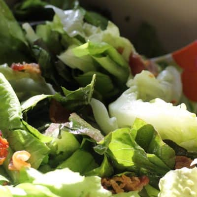 Lettuce, bacon, green onions, not bacon dressing in a white bowl