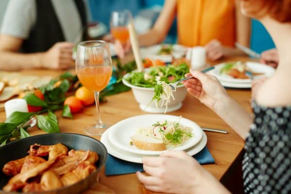 People eating around a table outdoors, salad on a white plate, blue napkin