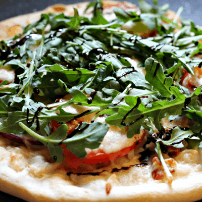 BLT Pizza Recipe - Easy Weeknight Meal. Topped with bacon, arugula, and tomatoes. #pizzarecipeeasy #bltpizza #weeknightmealidea
