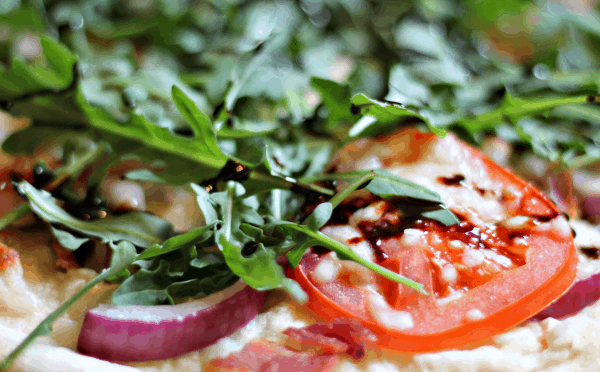 close-up of BLT Pizza with bacon, tomato, arugula, red onion, and balsamic glaze