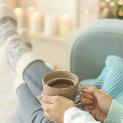 non descript woman holding a cup of coffee while relaxing via candlelight