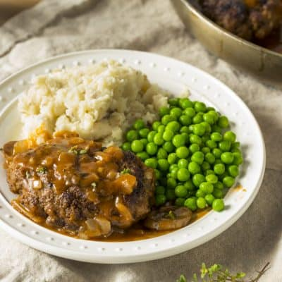 Homemade Savory Salisbury Steaks with mashed potatoes and peas on a white plate