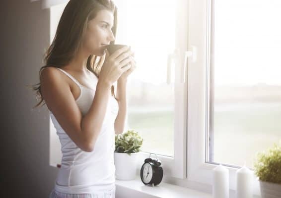 Woman staring out window while drinking a cup of coffee