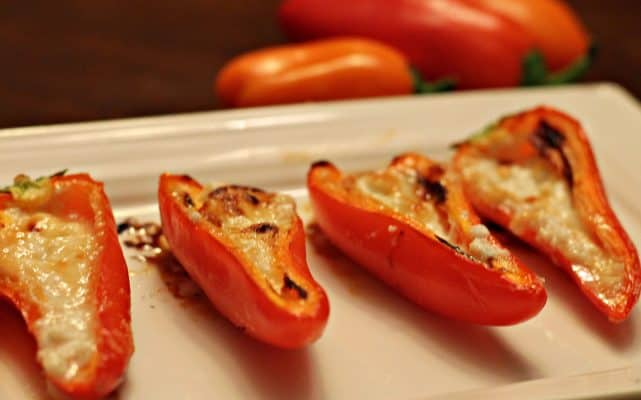 Mini red peppers stuffed with goat cheese and honey on a white tray