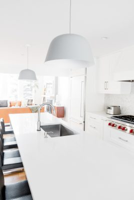 Picture of a modern kitchen counter with chairs and dome lamps