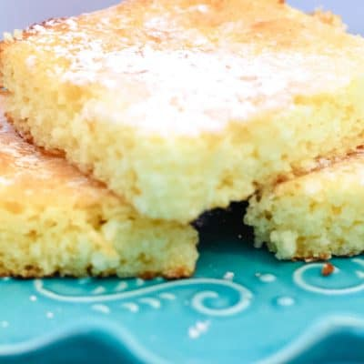 3 lemon cake bars stacked on a turquoise cake stand