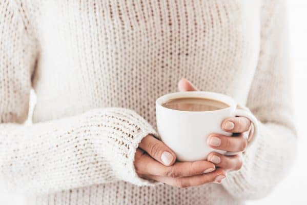 Warming cup of coffee in the hands of women