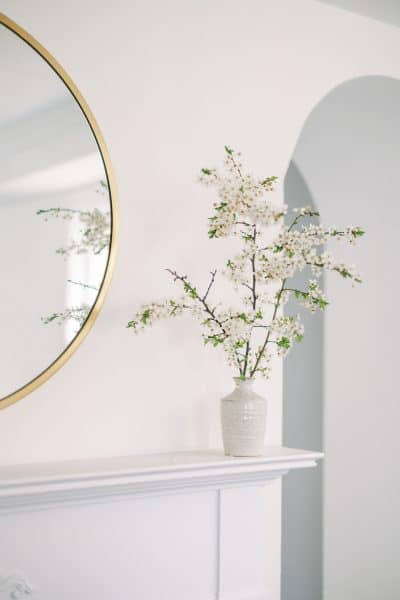face of flowers on a shelf next to a round mirror