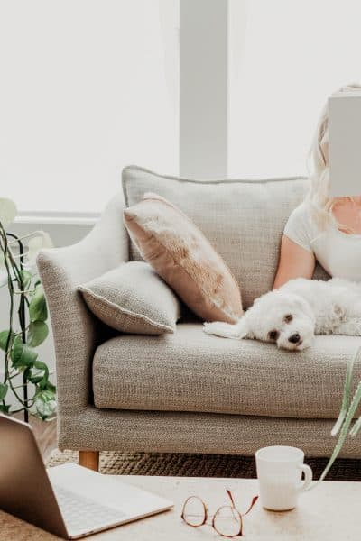 woman relaxing with her dog while reading