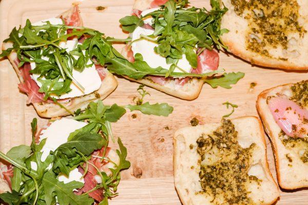 3 half a ciabatta roll with prosciutto, mozzarella, and arugula on top