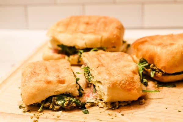3 prosciutto and mozzarella paninis on a cutting board