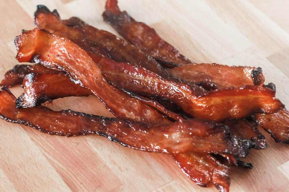 Caramelized Bacon on a brown cutting board