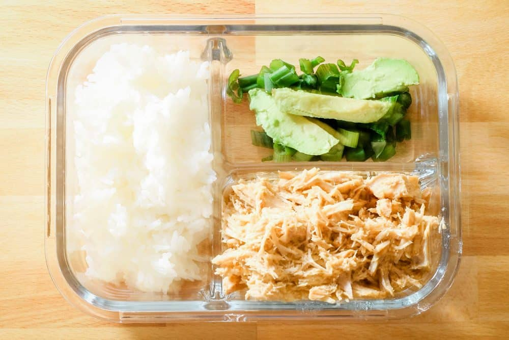Leftover mexican carnitas in a glass bento box with rice and vegetables
