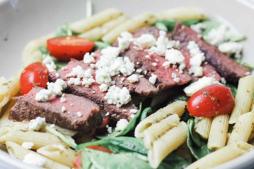 steak pasta with spinach in a bowl