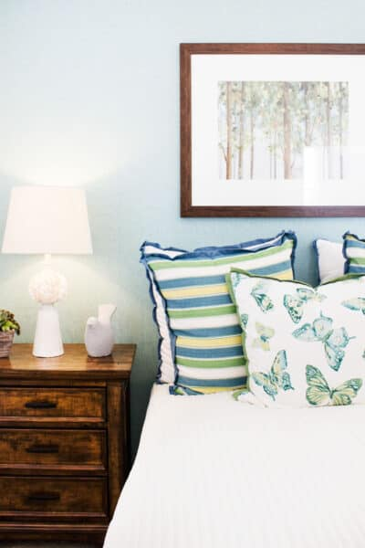 cozy bed with throw pillows next to a night stand with a lamp on it