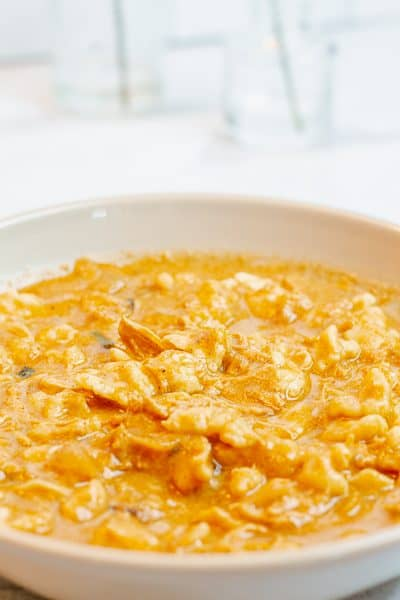 gray bowl filled with chicken paprikash on a white table