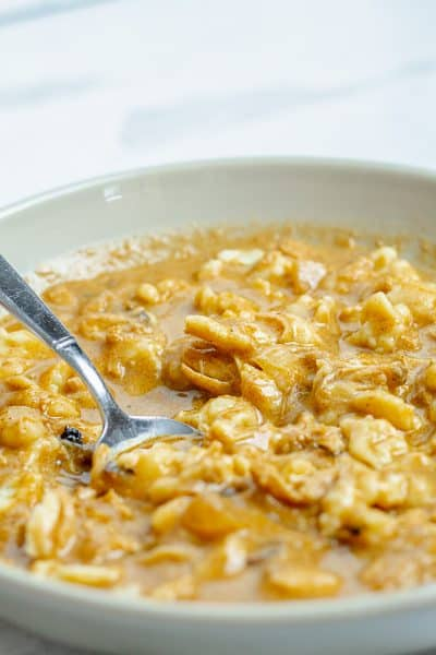 close up of a bowl with a spoon full of chicken and spaetzels