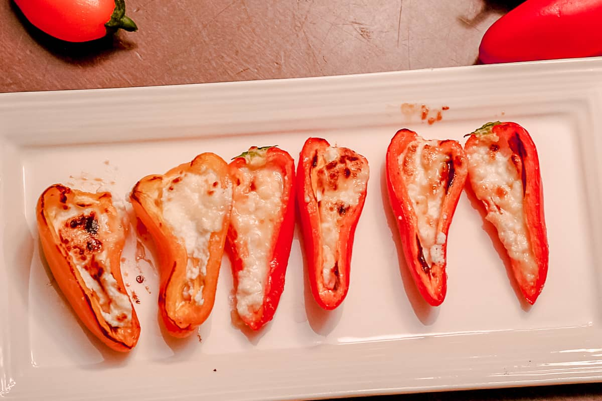 Red Mini-Peppers stuffed with baked goat cheese on a white tray