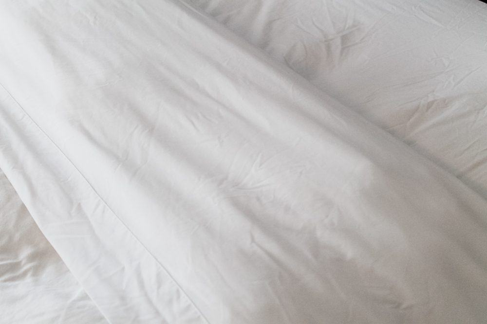 close up of flat sheet and duvet folded back on a bed