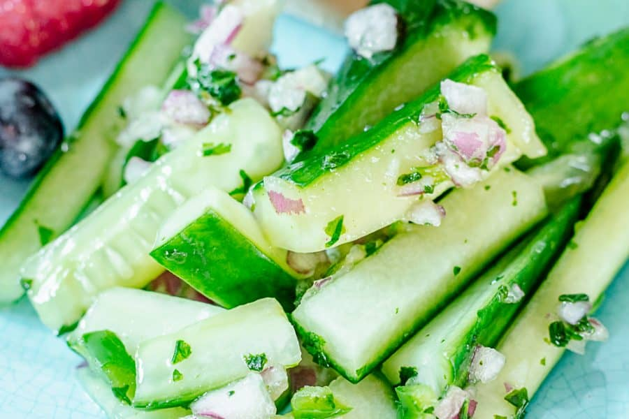close up on spicy cucumber salad on a teal plate