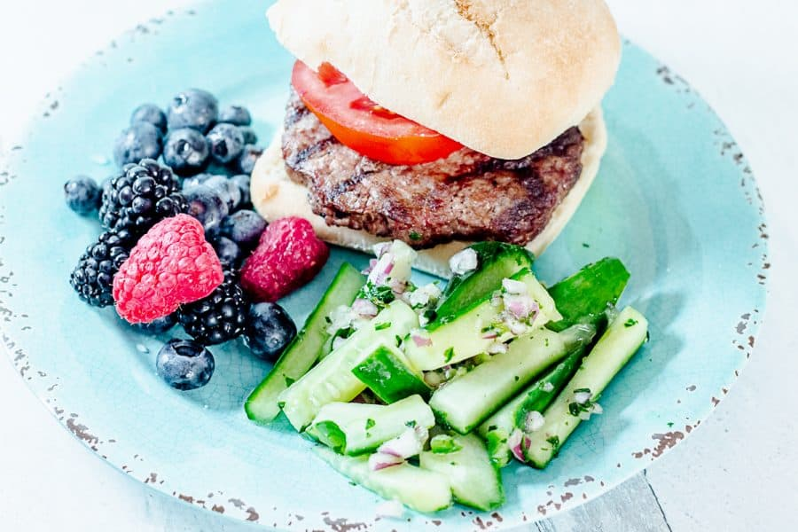 hamburger, mixed berries, and matchstick cucumber salad on a teal plate