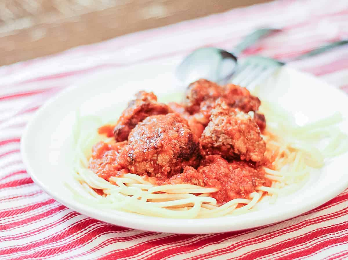 Close-up of a plate of homemade meatballs on a bed of noodles
