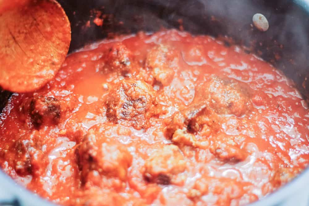 close up of a pot of simmering pasta sauce and meatballs