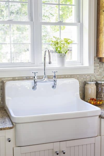 Bright kitchen window above farmhouse sink with summer hygge elements