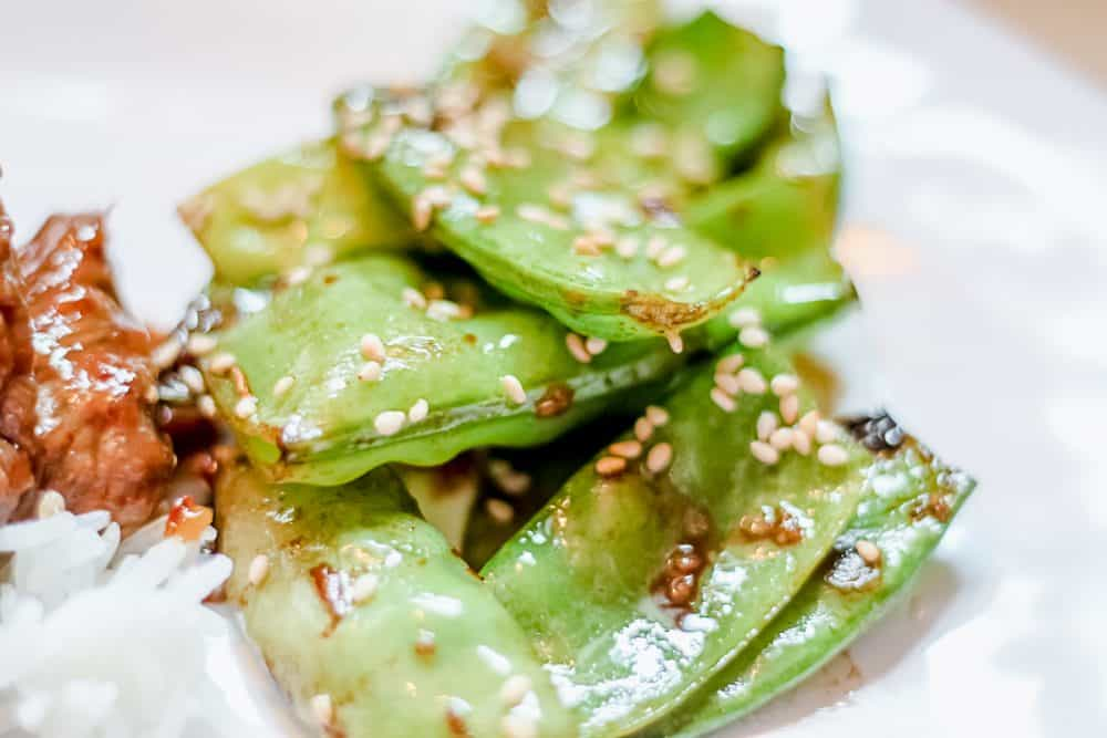 Sesame Snap Peas on white plate with rice and beef in background