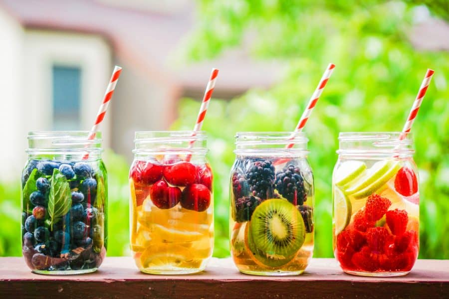 four mason jars filled with fruit infused water on a ledge