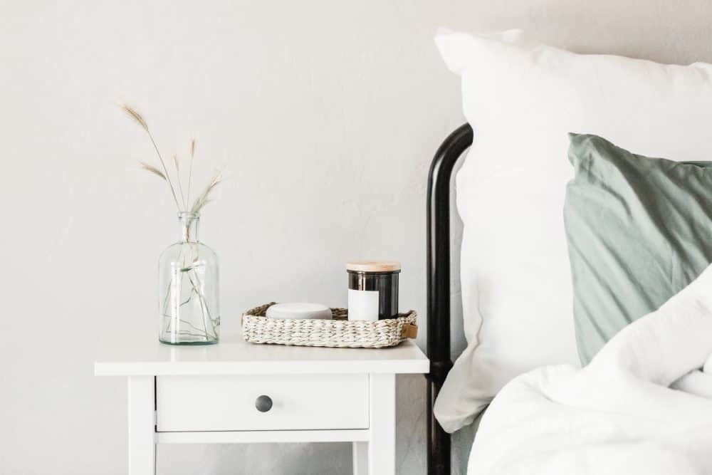 Close up of a comfortable bed and a white wooden nightstand