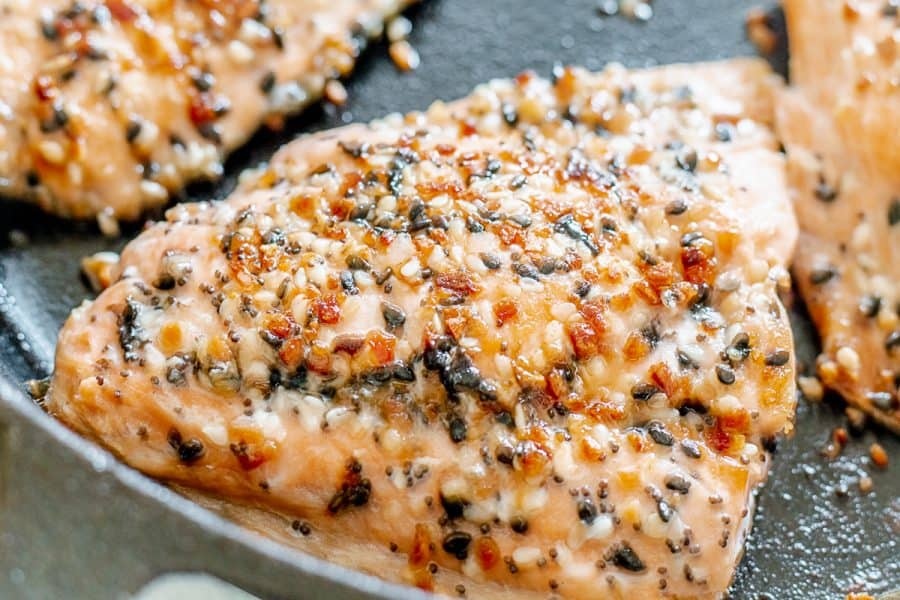 Salmon cooking in a cast iron pan