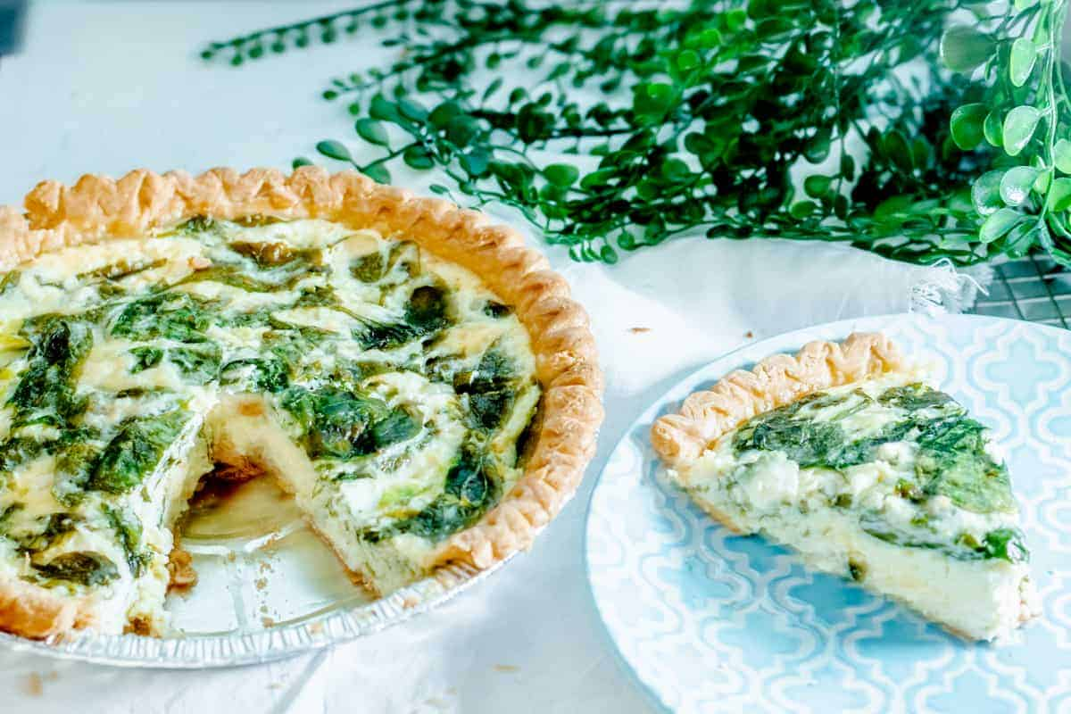 spinach quiche with a piece missing and blue plate containing slice of quiche