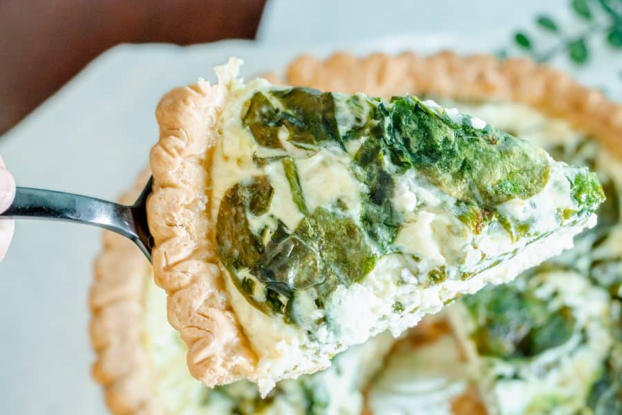 slice of fresh spinach and feta and swiss cheese quiche