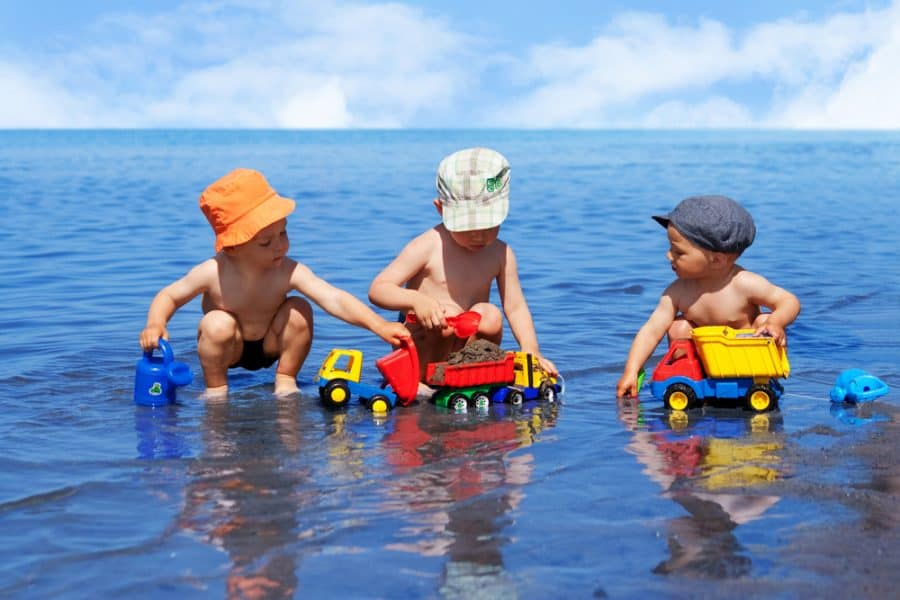 3 boys playing with trucks in a lake