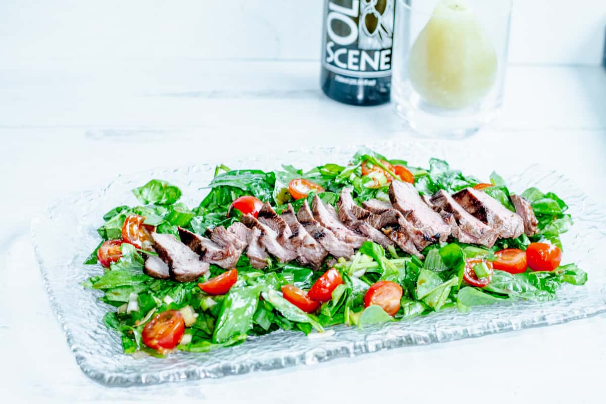 tray of green salad topped with rosemary marinade steak