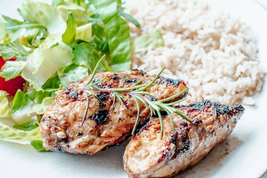 rosemary grilled chicken on a plate with rice and salad