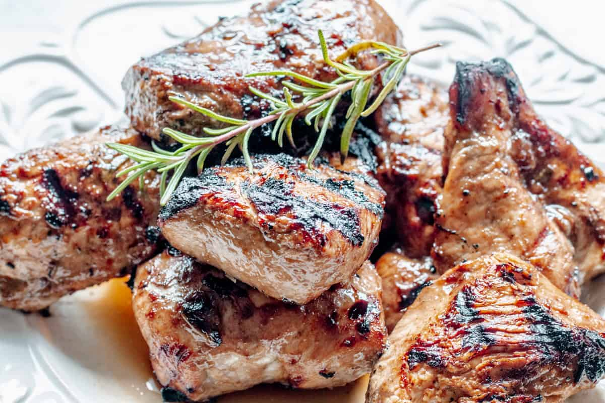 close up of plate of grilled chicken topped with a swig of rosemary