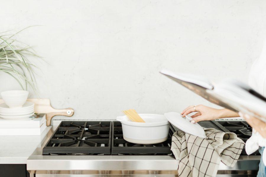 non descript woman cooking a cozy meal of pasta at a stove top