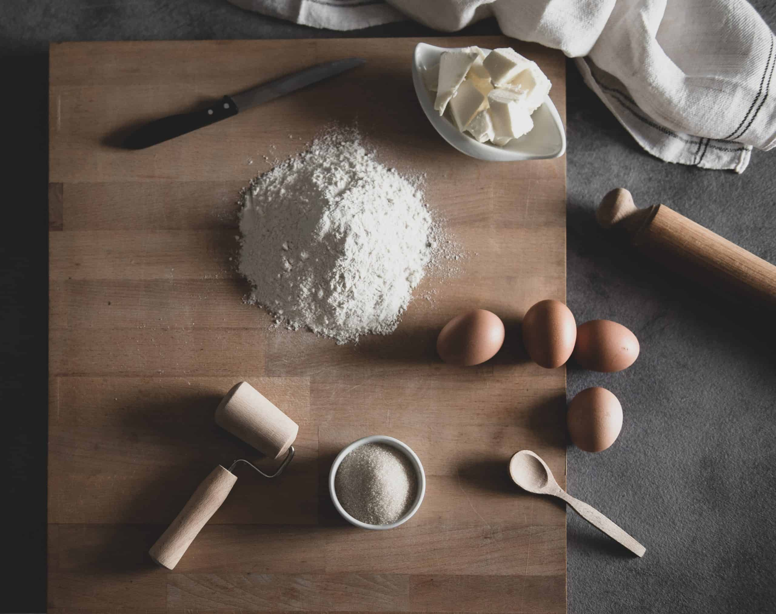 wooden cutting board with eggs, flour, and butter