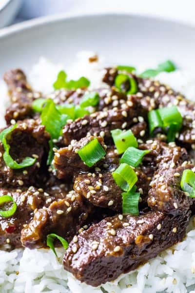 close up of mongolian beef over rice with green onions