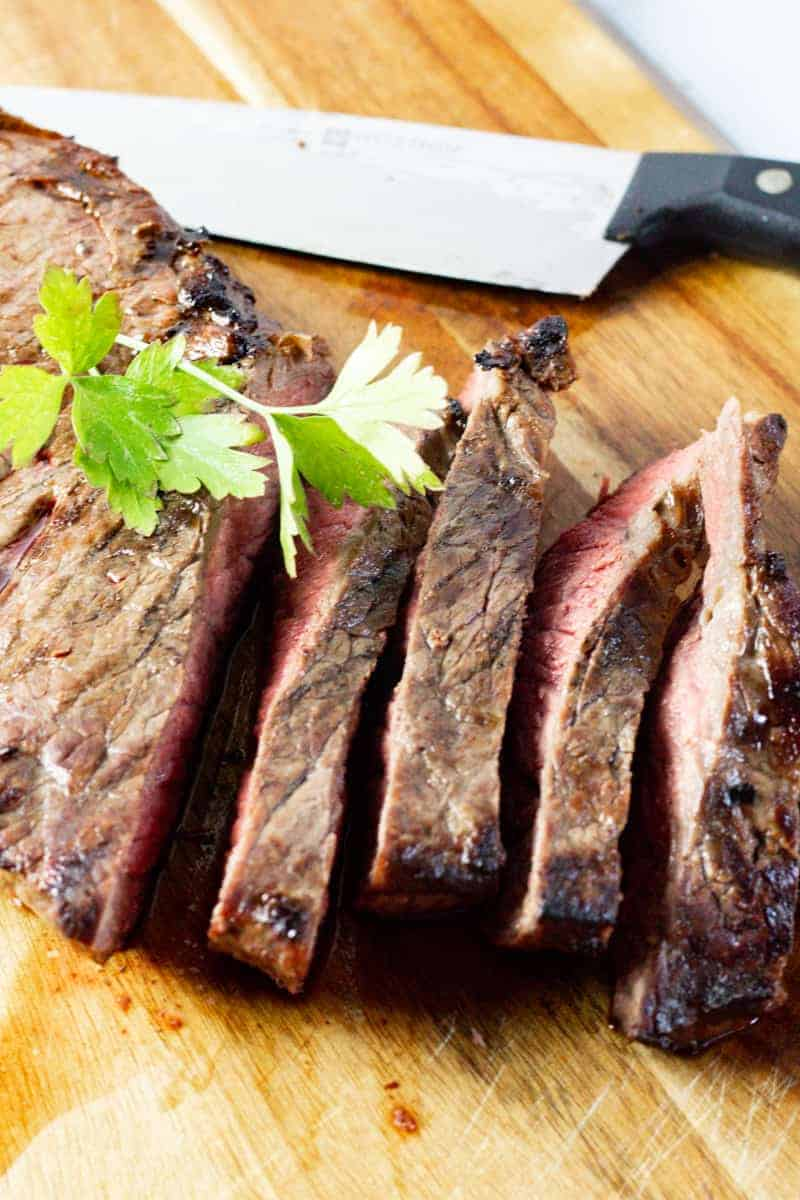 sliced marinated steak on a wooden cutting board