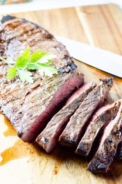 sliced marinated london broil on a wooden cutting board