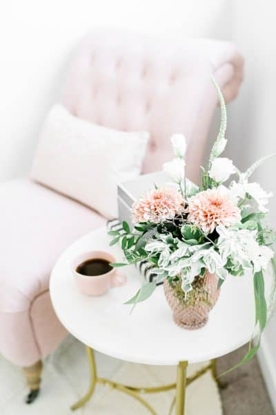 end table with flowers and coffee cup next to a cozy chair