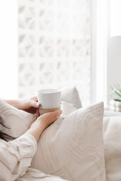 non-descript woman experiencing hygge on a cozy couch with a mug
