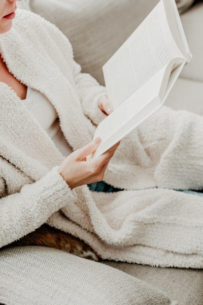 non-descript woman in a cozy sweater reading