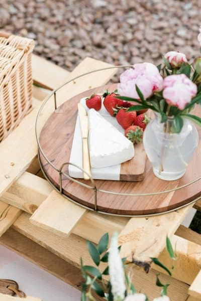 round wooden tray with cheese, strawberries, and flowers